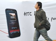 A man walks past a billboard displaying a handset of Taiwan smartphone maker HTC in Taipei. Taiwan's leading smartphone maker HTC Thursday hailed as a victory a British court ruling that it did not infringe on a patent owned by the US technology giant Apple