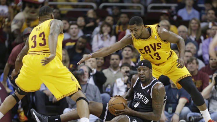 Cleveland Cavaliers' Alonzo Gee (33) and Tristan Thompson (13) loom over Brooklyn Nets' Andray Blatche (0) during the first quarter of an NBA basketball game Wednesday, April 16, 2014, in Cleveland. (AP Photo/Tony Dejak)