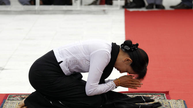 Myanmar opposition leader Aung San Suu Kyi pays respect at the tomb of her late father Gen. Aung San during a ceremony to mark the 65th anniversary of his 1947 assassination, at the Martyrs' Mausoleum in Yangon, Myanmar on Thursday, July 19, 2012.  For the first time in decades, Myanmar state television broadcast the memorial ceremony for the country's independence hero, the latest sign of change in the former pariah nation.  (AP Photo/Khin Maung Win)
