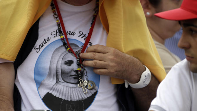 """Faithful wearing a shirt with a portrait of Laura di Santa Caterina da Siena Montoya, of Colombia, wait for the arrival Pope Francis for a canonization Mass in St. Peter's Square at the Vatican, Sunday, May 12, 2013. Pope Francis on Sunday gave the Catholic church new saints, including hundreds of 15th-century martyrs who were beheaded for refusing to convert to Islam, as he led his first canonization ceremony Sunday in a packed St. Peter's Square. Francis also gave Colombia its first saint: a nun who toiled as a teacher and spiritual guide to indigenous people in the 20th century. With Colombia's president, Juan Manuel Santos, among the VIPS in a crowd of tens of thousands, the pope held out Laura of St. Catherine of Siena Montoya y Upegui as a potential source of inspiration, with her """"example of harmony and reconciliation'' to that nation's peace process, attempted after decades-long conflict between rebels and government forces. (AP Photo/Gregorio Borgia)"""