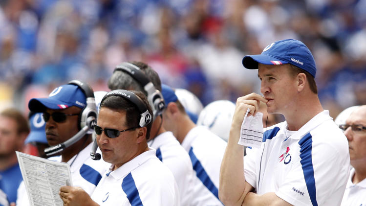 Injured Indianapolis Colts quarterback Peyton Manning, right, joins offensive coordinator Clyde Christensen on the sideline in the first quarter of an NFL football game against the Kansas City Chiefs in Indianapolis, Sunday, Oct. 9, 2011. (AP Photo/AJ Mast)