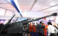 Exhibition visitors mill about a Howitzer displayed by Singapore Technologies Kinetics at the DefExpo 2010 in New Delhi. India has blacklisted six armament firms --including Singapore Technologies Kinetics -- for 10 years for their alleged role in a 2009 weapons bribery scandal