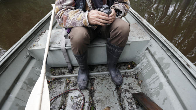 Florence resident Robin Powers has his boots, paddle and camera as he surveys flooding on Roundtree Road along the Lynches River in Effingham, S.C., Tuesday, Oct. 6, 2015. The Carolinas saw sunshine Tuesday after days of inundation, but it could take weeks to recover from being pummeled by a historic rainstorm that caused widespread flooding and multiple deaths. (AP Photo/Gerry Broome)