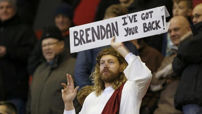 A Liverpool fan holds a sign before their English Premier League soccer match against Arsenal at Anfield in Liverpool