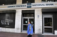 A woman passes by a closed branch of Greece's National Bank in Athens on February 23, 2011. Greece's biggest lender National Bank on Friday said it had posted a nine-month loss of 2.45 billion euros ($3.2 billion) while number two Alpha Bank said it had lost 711.8 million euros over the same period