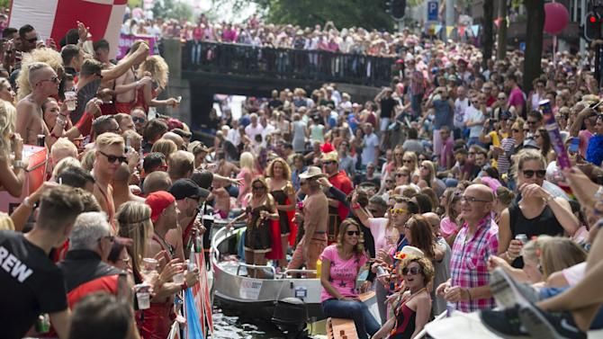 Participants of the 20th Canal Gay Parade celebrate on a boat in the Prinsengracht in Amsterdam, the Netherlands