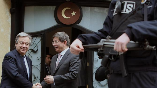 A Turkish security guard stands as United Nations High Commissioner for Refugees, UNHCR, chief Antonio Guterres, left, and Turkey's Foreign Minister Ahmet Davutoglu pose for cameras before a meeting in Ankara, Turkey, Sunday, March 10, 2013. Guterres will wisit Syrian refugee camps along the border between Turkey and Syria on Sunday.(AP Photo/Burhan Ozbilici)