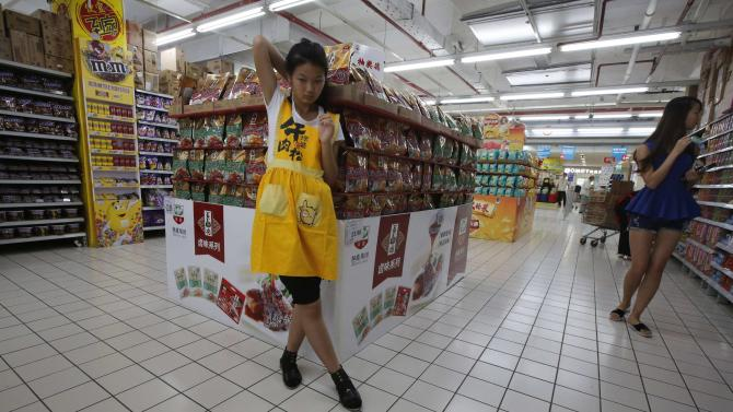 A worker waits for customers at a supermarket in Beijing