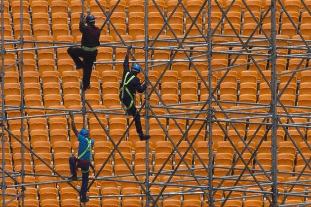 Workers climb scaffolding while constructing a stage ahead of Mandela's national memorial service in Johannesburg