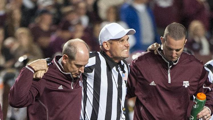 Referee Matt Loeffler, center, is helped off the field by Texas A&M staff after being injured during the second quarter of an NCAA college football game against Missouri, Saturday, Nov. 24, 2012, in College Station, Texas. (AP Photo/Dave Einsel)
