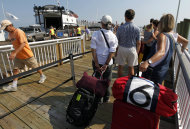 Passengers waiting to depart the Island of Martha's Vineyard, right, stand in line to board a ferry in Oak Bluffs, Mass., Friday, Aug. 26, 2011. The Steamship Authority, which operates ferries between the island and the mainland, has added additional vessels to the schedule in anticipation of the arrival of Hurricane Irene. Passengers and vehicles arriving on the island are seen behind. (AP Photo/Steven Senne)