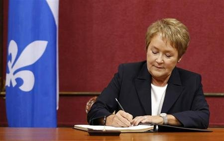 Quebec's Premier-elect Pauline Marois signs documents during the swearing-in ceremony for the Parti Quebecois members of the National Assembly (MNA) at the Quebec Legislature