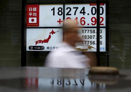 A pedestrian walks past electronic boards showing the Japan's Nikkei average outside a brokerage in Tokyo