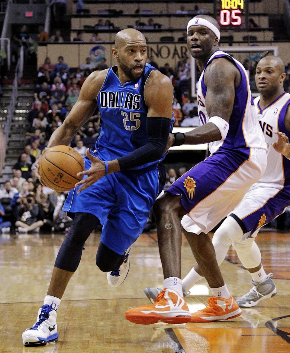 Dallas Mavericks' Vince Carter (25) drives past Phoenix Suns' Jermaine O'Neal during the first half of an NBA basketball game, Thursday, Dec. 6, 2012, in Phoenix. (AP Photo/Matt York)