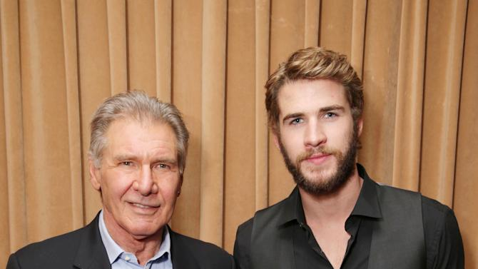"""Harrison Ford, cast member in the upcoming film """"Ender's Game"""" and Liam Hemsworth, cast member in the upcoming film """"The Hunger Games: Catching Fire"""" at Lionsgate Presentation at 2013 CinemaCon, on Thursday, April, 18th, 2013 in Las Vegas. (Photo by Eric Charbonneau/Invision for Lionsgate/AP Images)"""