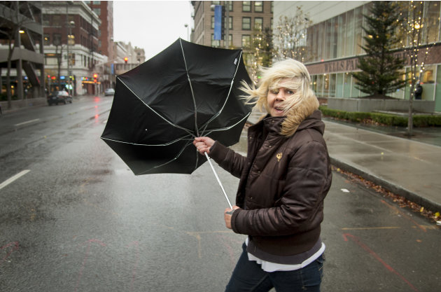 During a strong gust of wind, Michele Purkey's umbrella flips back as she crosses the intersection of First Avenue and Wall Street on Monday, Nov. 19, 2012, in downtown Spokane, Wash. Residents in Was