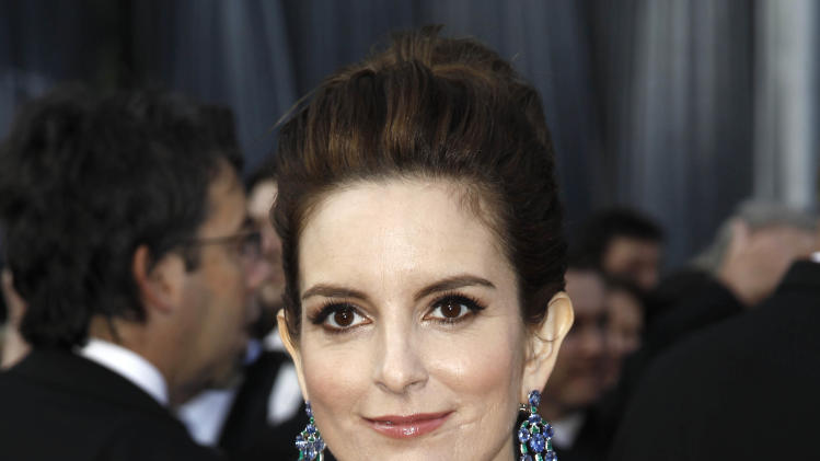"FILE - This Feb. 26, 2012 file photo shows Tina Fey arriving at the 84th Academy Awards in the Hollywood section of Los Angeles. On Tuesday night, Fey received Audie Awards for Audio Book of the Year and best Biography/Memoir for her narration of her million-selling ""Bossypants."" (AP Photo/Matt Sayles, file)"