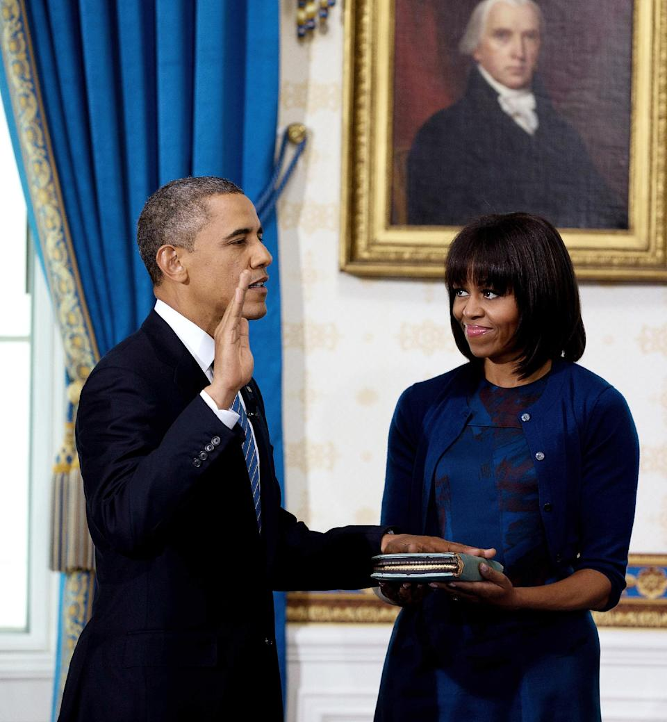 President Barack Obama is officially sworn-in by Chief Justice John Roberts, not pictured, in the Blue Room of the White House Sunday, Jan. 20, 2013, in Washington, as first lady Michelle Obama holds the Robinson Family Bible. (AP Photo/Doug Mills, The New York Times, Pool)