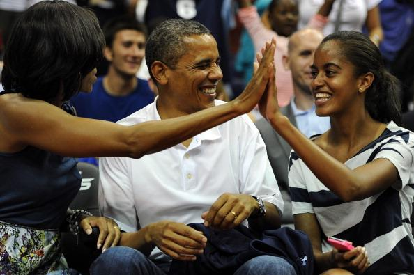 President Barack Obama shares a laugh with his wife Michelle and daughter Malia, as the US Senior Men's National Team and Brazil play during a pre-Olympic exhibition basketball game at the Verizon Cen