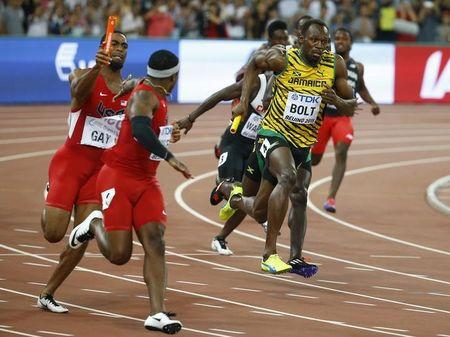 Rodgers of the U.S. receives the baton from his teammate Gay outside the exchange area as Bolt of Jamaica competes in the men's 4 x 100 metres relay final during the 15th IAAF World Championships at the National Stadium in Beijing