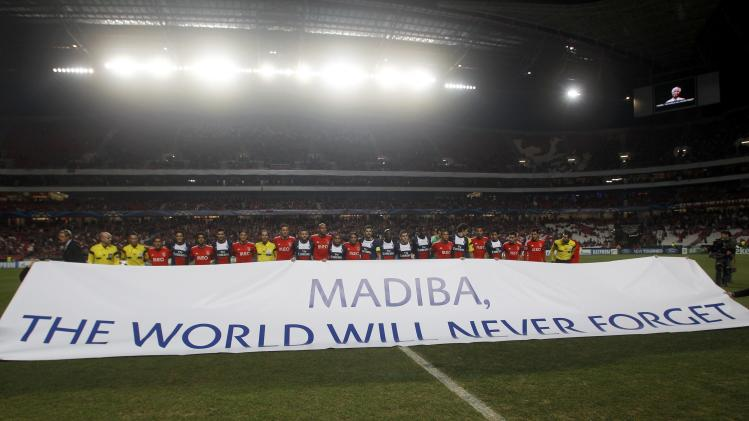 Benfica and Paris St Germain players stand behind a banner in tribute to the life of Nelson Mandela before their Champions League soccer match in Lisbon