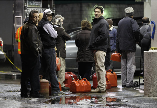 People line up with containers as they wait in line to get gas at a Hess station in the Brooklyn borough of New York where gas is still scarce, Thursday, Nov. 8, 2012. Fuel shortages and distribution