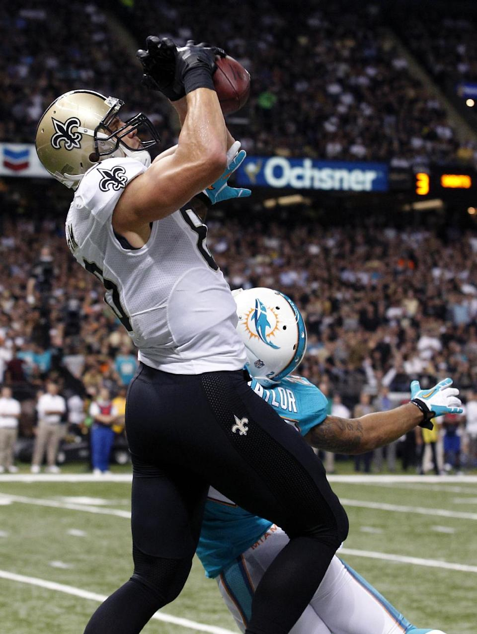 New Orleans Saints tight end Jimmy Graham (80) pulls in a touchdown reception over Miami Dolphins cornerback Jamar Taylor (22) in the first half of an NFL football game in New Orleans, Monday, Sept. 30, 2013. (AP Photo/Bill Haber)