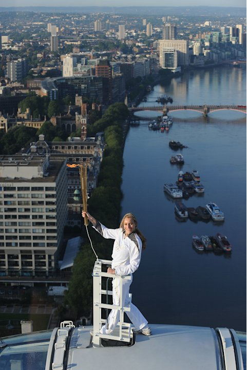 In this photo provided by LOCOG, Amelia Hempleman-Adams poses with the Olympic Flame on top of a London Eye pod on the Torch Relay leg through London. Opening Ceremonies for the 2012 London Olympics w