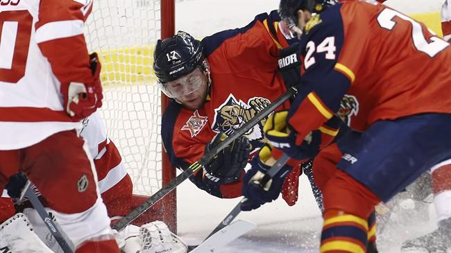 Florida Panthers' Jesse Winchester (17) tries a shot on goal against Detroit Red Wings goalie Jmmy Howard during the first period of a NHL hockey game in Sunrise, Fla., Tuesday, Dec. 10, 2013. (AP Photo/J Pat Carter)