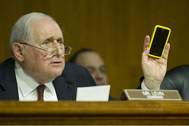 US Senator Carl Levin holds up his Apple iPhone as he questions Apple Chief Executive Officer Tim Cook, May 21, 2013