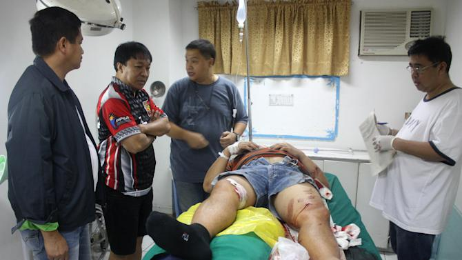 In this photo released by the Philippine National Police Quezon Provincial Director's Office, Quezon provincial police chief Valeriano de Leon, left, visits a wounded policeman after a shootout with suspected criminals at a checkpoint along a road in the town of Atimonan in Quezon province, about 140 kilometers (100 miles) southeast of Manila, in the Philippines Sunday, Jan. 6, 2013. Philippine army special forces and police killed 13 suspected criminals in a gunbattle Sunday in the latest violence to erupt in the country in the past week. (AP Photo/Philippine National Police Quezon Provincial Director's Office)