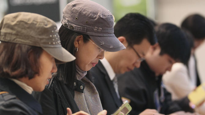 Visitors operate Samsung Electronics' Galaxy S4 smartphones at a showroom of its headquarters in Seoul, South Korea, Friday, April 26, 2013. Samsung Electronics Co. said Friday its first-quarter net income jumped to a record high because sales growth in smartphones continued even before the launch of the Galaxy S4 during a typically slow season for the electronics market. (AP Photo/Ahn Young-joon)
