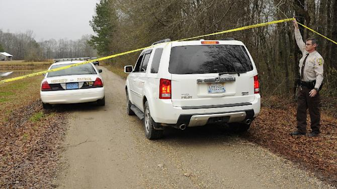 A Walker County sheriff's deputy lifts crime scene tape for investigators as National Transportation Safety Board officials continue investigate the fatal crash Tuesday night of a small plane that was reported stolen near Jasper, Ala., Wednesday, Jan. 2, 2013. Walker County sheriff's Chief Deputy James Painter says authorities are still investigating but believe the teenagers took the plane without permission before it crashed Tuesday night. (AP Photo/AL.com, Joe Songer) MAGS OUT