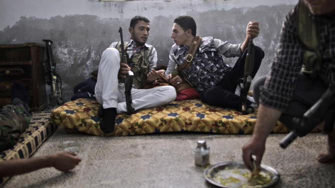 A Syrian rebel fighter, right, eats while others chat as they wait for transportation to go and fight government forces in Aleppo, at their headquarters in Suran, on the outskirts of Aleppo, Syria, Monday, Sept. 10, 2012. (AP Photo/Muhammed Muheisen)