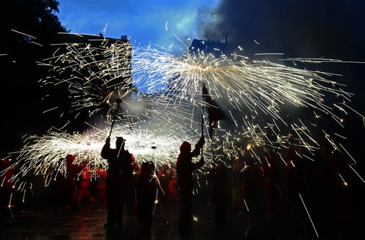 "Revelers hold torches as they take part in 'Correfoc' (Run with fire) party in Barcelona, Spain, Sunday, July 15, 2012. Correfocs or ""fire-runs"" are among the most striking features present in Catalan"