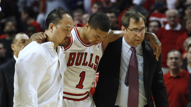 Chicago Bulls' Rose is helped off court during second half of their NBA Eastern Conference quarter-final playoff basketball game against Philadelphia 76ers in Chicago
