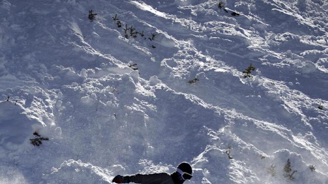 This Nov. 13, 2012 photo shows a snowboarder going down a slope at the Brighton Ski Resort along the Wasatch Range, in Utah. The Brighton Ski Resort is in middle of the Wasatch Range's 7 resorts. If the resorts were to be combined, the Utah resorts could offer North America's largest skiing complex _ three times the size of Vail and twice as big as Whistler Blackcomb in British Columbia. (AP Photo/Rick Bowmer)