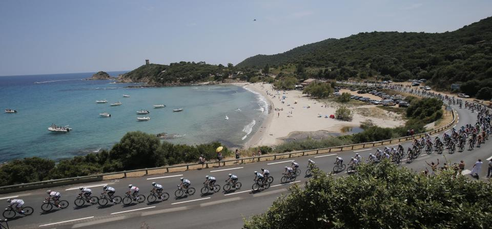 The pack rides along the coast line of the Mediterranean Sea during the first stage of the 100th edition of the Tour de France cycling race over 213 kilometers (133 miles) with start in Porto Vecchio and finish in Bastia, Corsica island, France, Saturday June 29, 2013.(AP Photo/Christophe Ena)