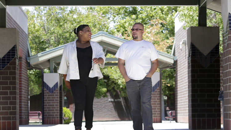 "In this photo taken Friday, July 11, 2014, Elk Grove Unified School District teacher Michael Jones and his former student Kandance Stagner, a foster child, walk around Laguna Creek High School, where Stagner recently graduated from, in Elk Grove, Calif. California, home to nearly one-fifth of the nation's children living in foster care, is embarking on a first-of-its-kind attempt to improve the academic lives of foster youth by giving schools more money to meet their special learning and emotional needs and holding educators and administrators responsible for producing results. As part of a new school funding formula the state will direct billions of extra dollars to districts based on how many students they have with low family incomes, learning to speak English or in foster care. Six years ago, Jones, who as a high school science teacher, founded a weekly class where students in foster care could gather to discuss their shared struggles, has doubts about the proposed program saying ""I've yet to see a (formula) that says we are going to fund people to care."" Stagner, 18, who has been in seven foster care settings since she was taken away from her mother in second grade, is preparing to attend college in Nebraska, something she attributes directly to Jones' unwavering support and nurturing family environment he created in his classroom. (AP Photo/Rich Pedroncelli)"