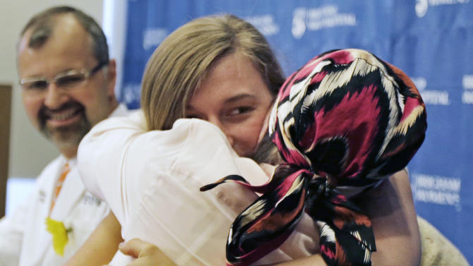 Marinda Righter, daughter of face donor Cheryl Denelli-Righter, embraces recipient Carmen Blandin Tarleton during a news conference at Brigham and Women's Hospital in Boston,Wednesday, May 1, 2013. Blandin Tarleton, the 44-year-old mother of two underwent the transplant in February, was injured after a 2007 attack in which her estranged husband doused her with industrial strength lye, burning more than 80 percent of her body. (AP Photo/Charles Krupa)