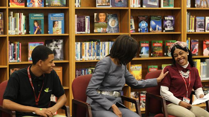 """First Lady Michelle Obama talks with students, including Joseph Jones, left, 11th grade and Kayla Pearson, 12th grade, right, during her visit to Harper High School in Chicago, Wednesday April 10, 2013. The first lady stressed education, telling the students the best thing they could do in life """"is really be serious about education."""" She told them that if they stay focused they """"can make it happen."""" (AP Photo/Chicago Tribune, Nancy Stone, Pool)"""