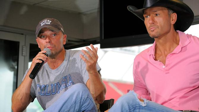 """Country singers Kenny Chesney, left, and Tim McGraw appear at a news conference to promote their """"Brothers of the Sun"""" concert tour on Friday June 1, 2012 in Tampa, Fla. The pair will kick off their tour on Saturday night in Tampa, Fla. (Photo by Scott Miller/Invision/AP)"""