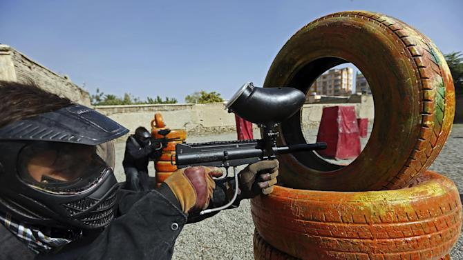 In this Friday, Aug. 22, 2014 photo, a man aims his gas-powered gun at his opponents as he plays in a friendly game of paintball in Kabul, Afghanistan. The arrival of recreational paintball to Afghanistan may seem peculiar to outsiders, especially in a country that's known decades of war, faces constant bombings and attacks by Taliban insurgents and is preparing its own security forces for the withdrawal of most foreign troops by the end of the year. However, it shows both the rise of a nascent upper and middle class looking for a diversion with the time to spare, as well as the way American culture has seeped into the country since the 2001 U.S.-led invasion to topple the Taliban. (AP Photo/Rahmat Gul)