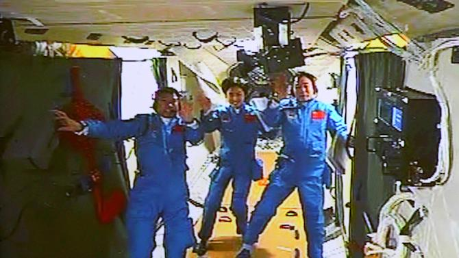 In this image made off the monitor screen at the Beijing Aerospace Flight Control Center and released by China's Xinhua News Agency, Chinese astronauts, from left, Liu Wang, Liu Yang and Jing Haipeng wave in the orbiting Tiangong-1 lab module Monday afternoon, June 18, 2012. They moved from Shenzhou-9 spacecraft to this module three hours after docking Monday. (AP Photo/Beijing Aerospace Control Center via Xinhua) NO SALES