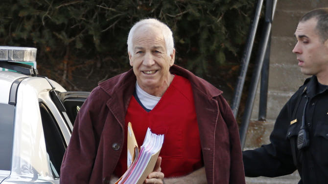 Former Penn State University assistant football coach Jerry Sandusky, left, arrives at the Centre County Courthouse for a post-sentence motion in Bellefonte, Pa., Thursday, Jan. 10, 2013. Thursday's hearing in Bellefonte is expected to delve into the legal challenges filed by Sandusky's lawyers, including their claim that a deluge of prosecution materials swamped the defense. Sandusky is serving a 30- to 60-year prison sentence after being convicted in June of 45 counts of child sexual abuse. (AP Photo/Gene J. Puskar)