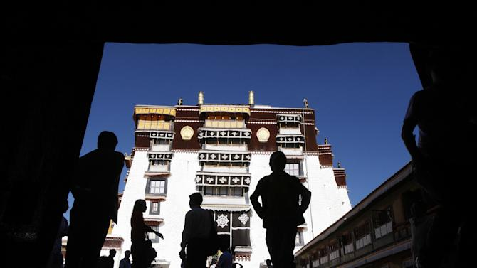 FILE - In this June 20, 2009 file photo, tourists walk through the Potala Palace, the former home of the Dalai Lama before he fled Tibet after a failed Tibetan uprising against Chinese rule in 1959, in Lhasa, the capital of Tibet, China. Tibet is seeing a boom in Chinese visitors, meaning that the government's latest ban on foreigners following self-immolation protests against Beijing's rule has barely dented the region's tourism industry. (AP Photo/Greg Baker, File)