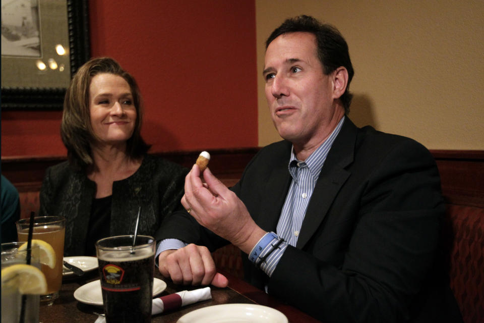 Republican presidential candidate, former Pennsylvania Sen. Rick Santorum, right, joined by his wife, Karen, eats cheese curds at a restaurant in West Bend, Wis., Sunday, April 1, 2012. (AP Photo/Jae C. Hong)