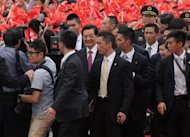 Chinese President Hu Jintao (C) smiles after arriving at Hong Kong&#39;s International airport on June 29. Hu has urged Hong Kong&#39;s restive people to embrace the motherland as he visited the financial citadel for the 15th anniversary of its return to rule by Beijing