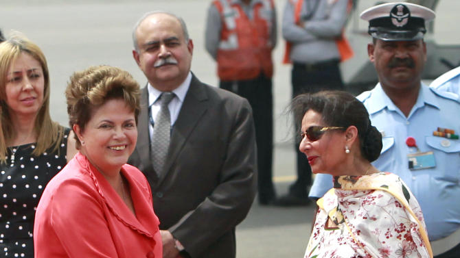 Brazil's President Dilma Rousseff, left, is greeted by India's Junior Minister for External Affairs Preneet Kaur on her arrival at the Palam Technical Airport in New Delhi, India, Tuesday, March 27, 2012. Rousseff is in India attending the BRICS (Brazil, Russia, India, China, South Africa) Summit which is to be held March 29 in New Delhi.  (AP Photo/ Mustafa Quraishi)
