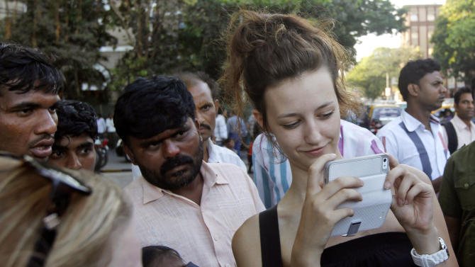 In this Tuesday, April 2, 2013 photo, a foreign tourist Amy Manson from England takes photographs as Indians watch her near the landmark Gateway of India in Mumbai, India. Violence against women, and the huge publicity generated by recent attacks here, is threatening India's $17.7 billion tourism industry with a new study showing tourism has plunged. (AP Photo/Rajanish Kakade)